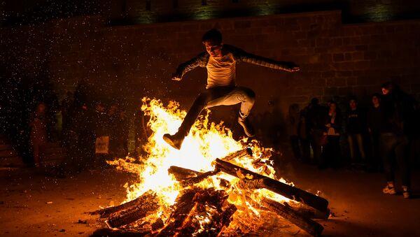 Мужчина прыгает через костер во время празднования вторника огня в Баку - Sputnik Азербайджан