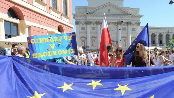 Девушки с флагами Евросоюза и Польши в ходе парада Шумана в Варшаве, 7 мая 2016 года - Sputnik Азербайджан