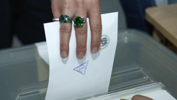 Избирательница опускает бюллетень в урну для голосования на выборах в Совет Старейшин на избирательном участке в Ереване - Sputnik Азербайджан