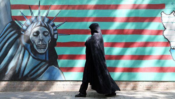 Женщина проходит мимо антиамериканской настенной росписи, изображающей Статую Свободы на стене бывшего американского посольства в Тегеране, фото из архива - Sputnik Азербайджан