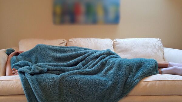Девушка спит на диване, полностью накрывшись одеялом, фото из архива - Sputnik Азербайджан