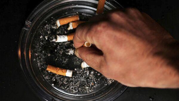 Мужчина тушит сигарету, фото из архива - Sputnik Азербайджан