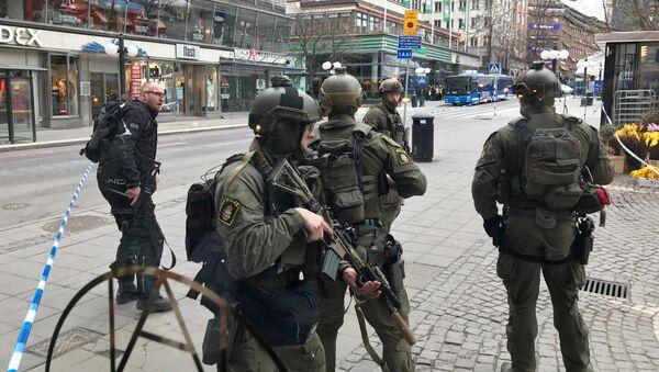 Полицейские в центре Стокгольма после наезда грузовика на людей на улице Дроттнинггатан. 7 апреля 2017 года - Sputnik Азербайджан