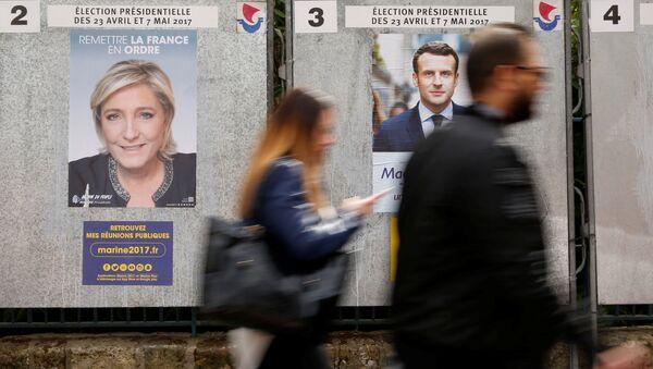 Люди проходят мимо агитационных плакатов лидера политической партии Марин Ле Пен, французского национального фронта и главы политического движения Эммануэля Макрона , фото из архива - Sputnik Азербайджан