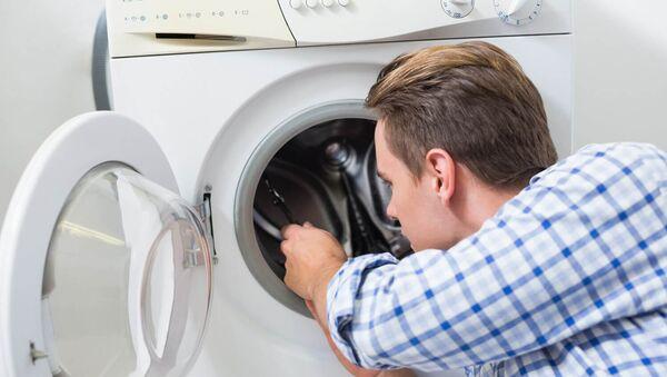 Мастер по ремонту бытовой техники осматривает стиральную машину, фото из архива - Sputnik Азербайджан