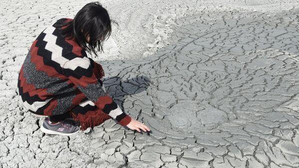 Женщина возле грязевого вулкана, архивное фото - Sputnik Азербайджан