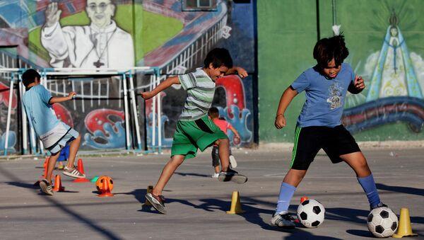 Дети играют в футбол перед фреской Папы Фрэнсиса в трущобах 1-11-14 в Буэнос-Айресе, Аргентина - Sputnik Азербайджан