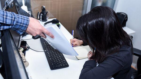 Мужчина передает документы женщине за столом - Sputnik Азербайджан