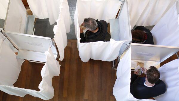 Избиратели выбирают своих кандидатов в кабинах для голосования на избирательном участке в Париже 23 апреля 2017 года во время первого тура президентских выборов во Франции - Sputnik Азербайджан