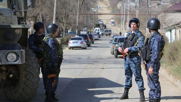 Сотрудники полиции на месте проведения контртеррористической операции у частного дома в Буйнакске, в ходе которой были уничтожены трое боевиков так называемой буйнакской группы. На месте спецоперации обнаружено оружие, боеприпасы и готовый к применению пояс смертника с зарядом - Sputnik Азербайджан
