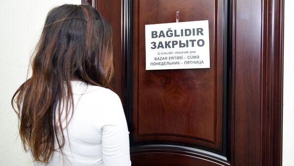Девушка стоит у закрытой двери - Sputnik Азербайджан