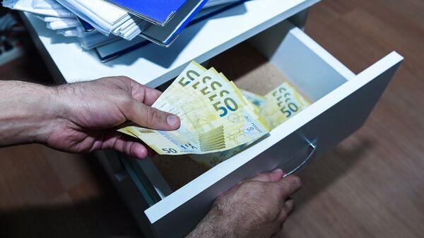 Мужчина прячет деньги  в ящик комода, фото из архива - Sputnik Азербайджан