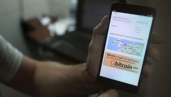 Демонстрация на смартфоне мобильного приложения для работы с криптовалютой биткоин, фото из архива - Sputnik Азербайджан