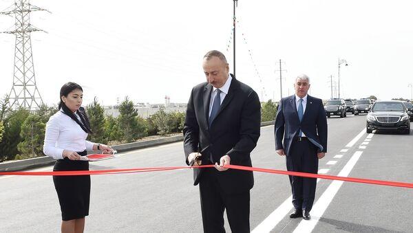 Президент Азербайджана Ильхам Алиев разрезает ленту, символизирующую открытии улицы Самеда Вургуна в поселке Пираллахи - Sputnik Азербайджан