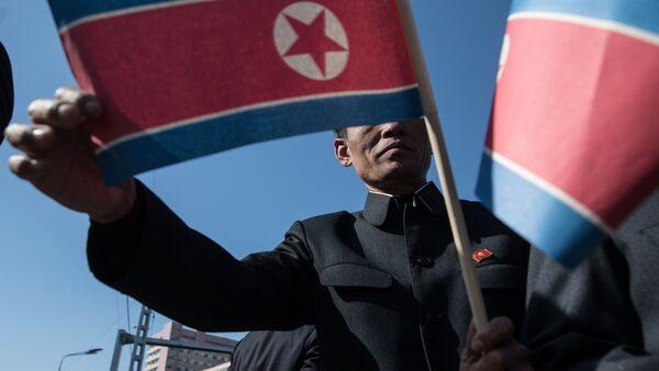Жители города с флагами КНДР во время торжественной церемонии открытия нового жилого комплекса на улице Рёмён в Пхеньяне - Sputnik Азербайджан