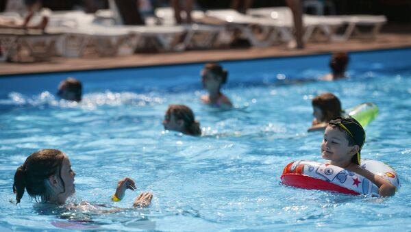 Люди купаются в бассейне - Sputnik Азербайджан