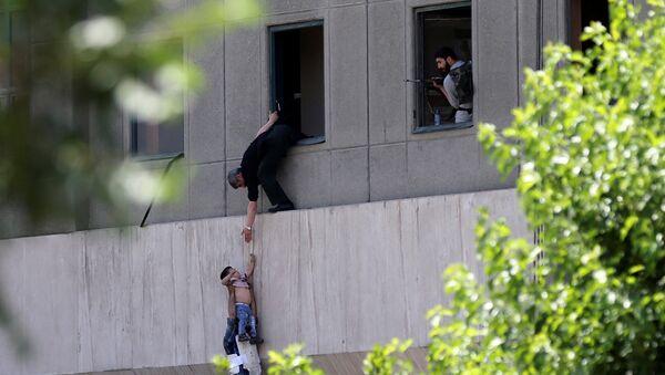 Человек передает ребенка охраннику из окна парламента Ирана в Тегеране - Sputnik Азербайджан