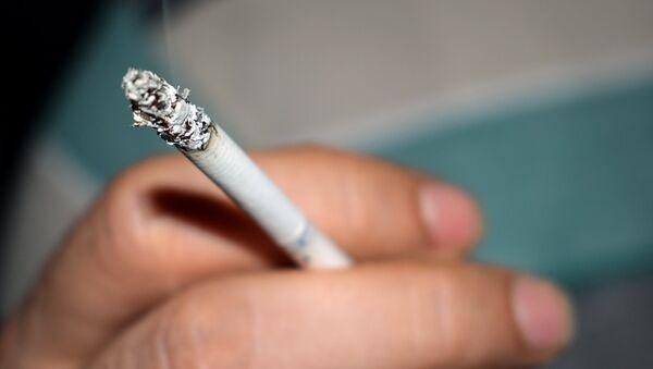 Мужчина держит в руке сигарету, фото из архива - Sputnik Азербайджан