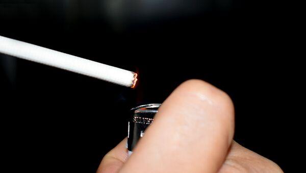 Мужчина закуривает сигарету, фото из архива - Sputnik Азербайджан