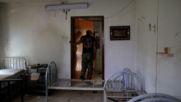 Солдат иракской армии осматривает заброшенную полевую больницу, используемую боевиками ИГ на западе Мосула, Ирак, 6 июня 2017 года - Sputnik Азербайджан