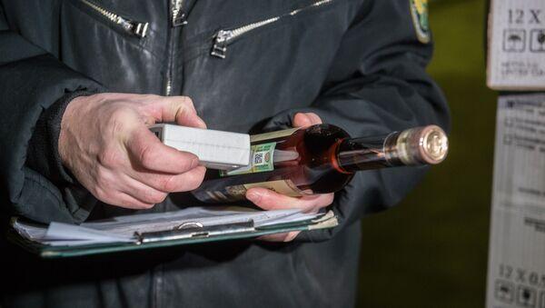 Сотрудник таможенного поста проверяет алкогольную продукцию на соответствия требованиям и нормам - Sputnik Азербайджан