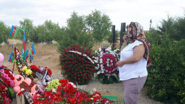 Оксана Алтунян у могилы двухлетней Захры Гулиевой и ее бабушки Сахибы Гулиевой - Sputnik Азербайджан