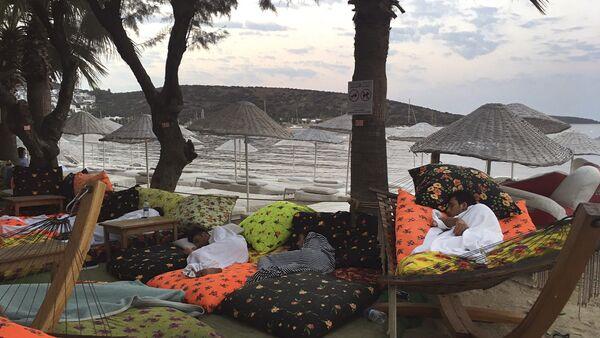 Мужчина лежит на берегу моря в Битезе, курортном поселке в 4 км от Бодрума, Турция, 21 июля 2017 года - Sputnik Азербайджан