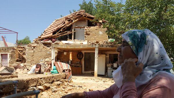 Женщина сидит во дворе своего дома, разрушенного землетрясением в деревне Ялычифтлик недалеко от курортного города Бодрум в провинции Мугла, Турция, 21 июля 2017 года - Sputnik Азербайджан