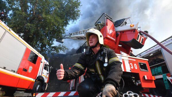 Сотрудник противопожарной службы во время тушения пожара в торговом центре Атом на Таганской площади в Москве - Sputnik Азербайджан