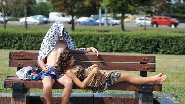 Молодые люди отдыхают на лавочке в жаркий летний день, фото из архива - Sputnik Азербайджан