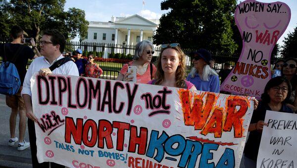 Протестующие призывают к мирным переговорам с Северной Кореей во время пикета перед Белым домом в Вашингтоне, США, 9 августа 2017 года - Sputnik Азербайджан
