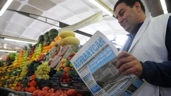 Продавец овощей и фруктов читает газету на Дорогомиловском рынке в Москве, 10 октября 2013 года - Sputnik Азербайджан
