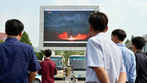 Жители северокорейской столицы следят за новостями о запуске ракеты средней дальности Hwasong-12 на электронном табло в Пхеньяне, Северная Корея, 30 августа 2017 года - Sputnik Азербайджан