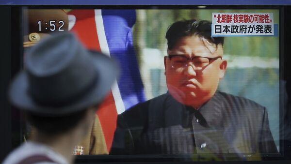 Мужчина в Токио смотрит телевизор, по которому выступает северокорейский лидер Ким Чен Ын, 3 сентября 2017 года - Sputnik Азербайджан
