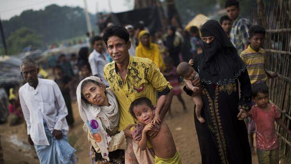 Прибывший в лагерь беженцев Кутупалонг рохинджа помогает пожилым членам семьи и ребенку - Sputnik Азербайджан