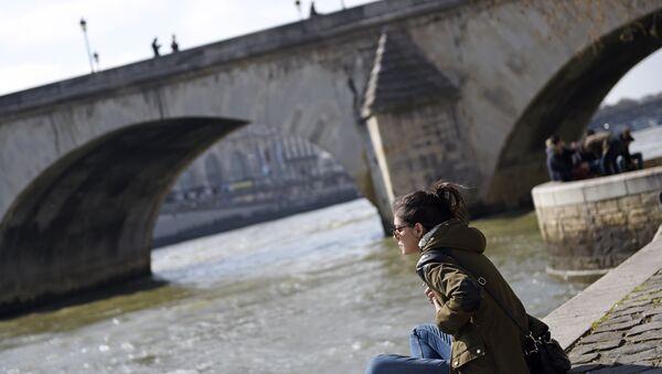 Женщина сидит на берегу реки Сена в Париже, фото из архива - Sputnik Азербайджан