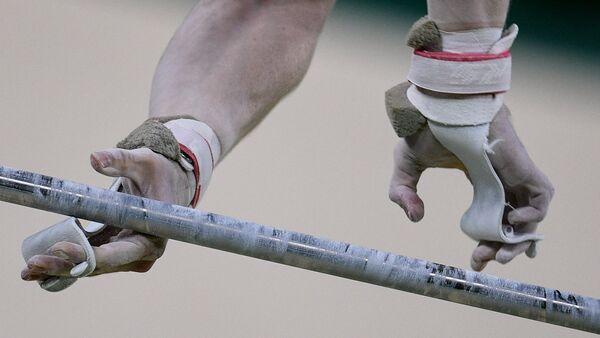 Спортсмен выполняет упражнения на перекладине на соревнованиях по спортивной гимнастике, фото из архива - Sputnik Азербайджан
