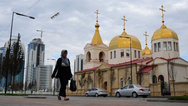 Женщина в хиджабе проходит по улице рядом с православной церковью Архангела Михаила на проспекте имени Ахмата Кадырова в Грозном, фото из архива - Sputnik Азербайджан