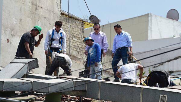 Люди на месте обрушившегося в результате землетрясения здания в в городе Мехико, Мексика, 19 сентября 2017 года - Sputnik Азербайджан