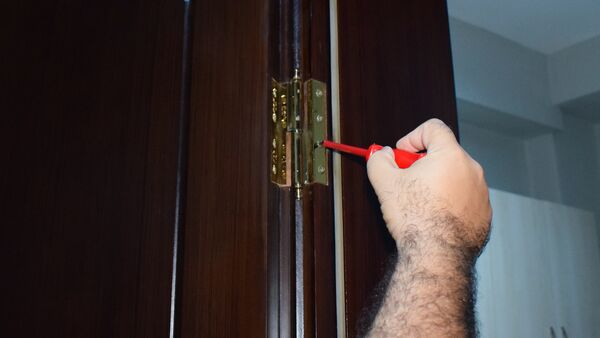 Мужчина демонтирует дверь, фото из архива - Sputnik Азербайджан
