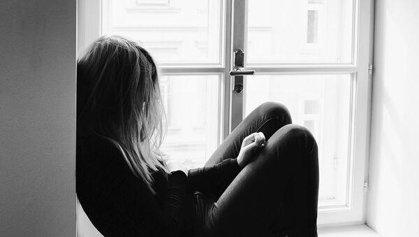 Сидящая в углу комнаты девушка - Sputnik Azərbaycan