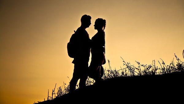 Силуэты мужчины и женщины на фоне заката. Архивное фото - Sputnik Азербайджан