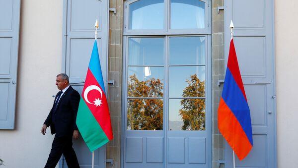 Охранник проходит мимо азербайджанского (слева) и армянского флага на открытии переговоров в Женеве, Швейцария - Sputnik Азербайджан