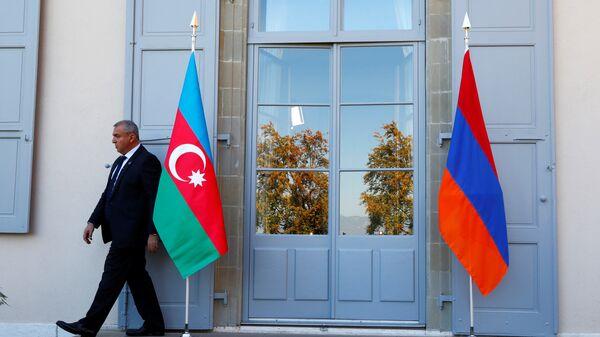 Охранник проходит мимо азербайджанского (слева) и армянского флага на открытии переговоров в Женеве, Швейцария - Sputnik Azərbaycan