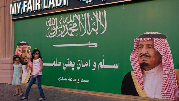 Девочки стоят рядом с плакатом, изображающим короля Саудовской Аравии Салмана бен Абдулазиза Аль Сауда и наследного принца Мохаммеда бин Салмана в Джидде, Саудовская Аравия, 10 ноября 2017 года - Sputnik Азербайджан