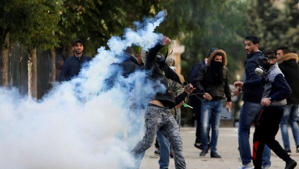 Палестинский протестующий бросает баллон со слезоточивым газом в сторону израильских военных во время столкновений в Вифлееме на Западном берегу, 7 декабря 2017 года - Sputnik Азербайджан