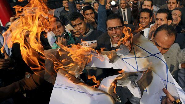 Протестующие кричат лозунги и сжигают израильский флаг во время антиизраильского протеста в Каире, Египет, 10 декабря 2017 года - Sputnik Азербайджан