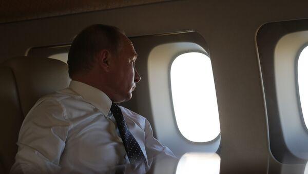Президент РФ Владимир Путин на борту президентского самолета во время полета на авиабазу Хмеймим в Сирии - Sputnik Азербайджан