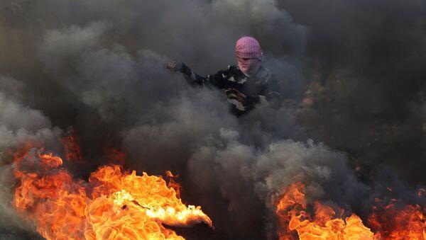 Протестующий во время столкновений на границе Палестины и Израиля в районе Рамаллы - Sputnik Azərbaycan