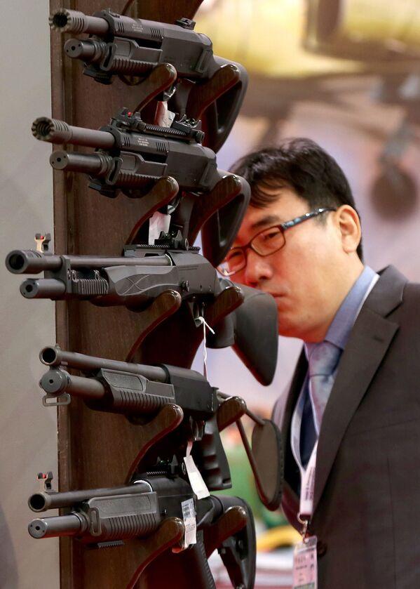 Посетитель осматривает ружья на международной выставке вооружения и военной техники Gulf Defence & Aerospace-2017 в Эль-Кувейте - Sputnik Азербайджан